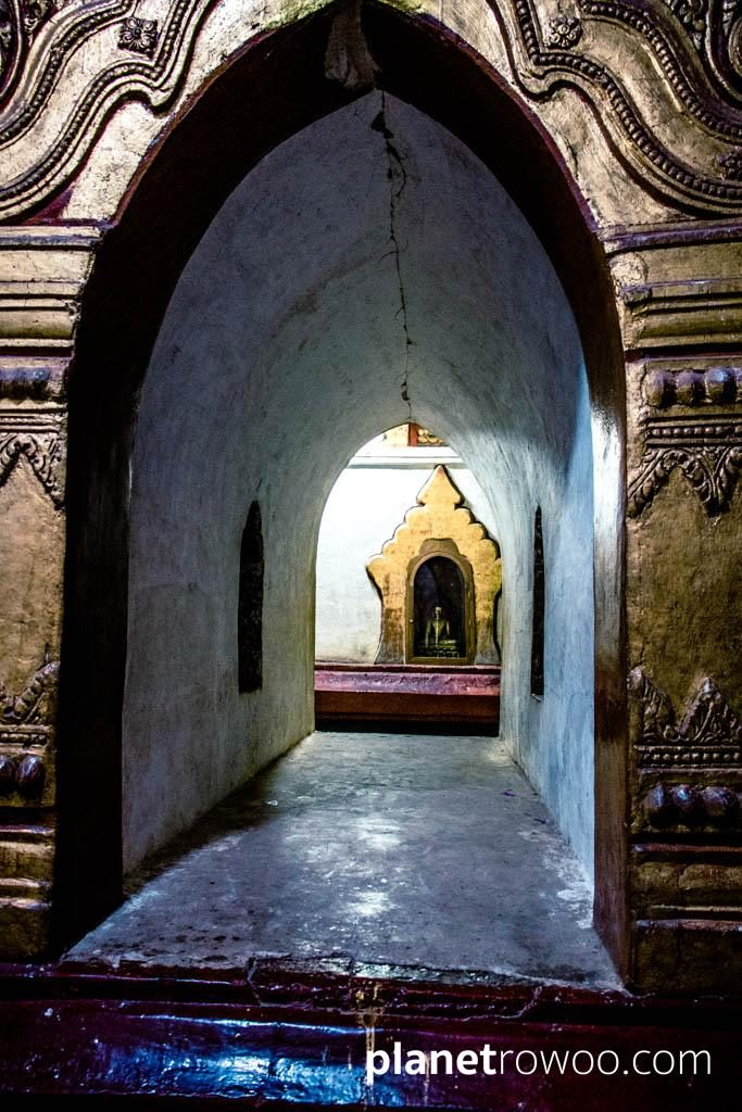 Passageway between the Ananda temple interior corridors with enshrined Buddha image visible in niche