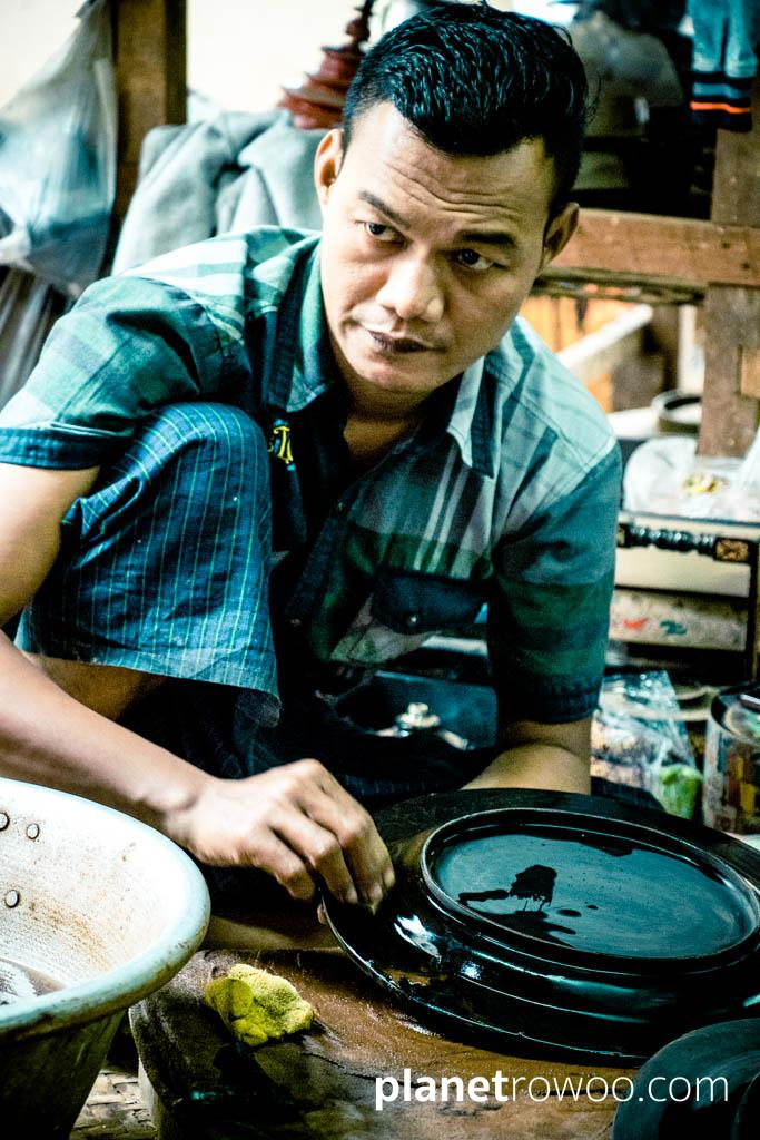 Applying lacquer to a lacquerware plate, Bagan