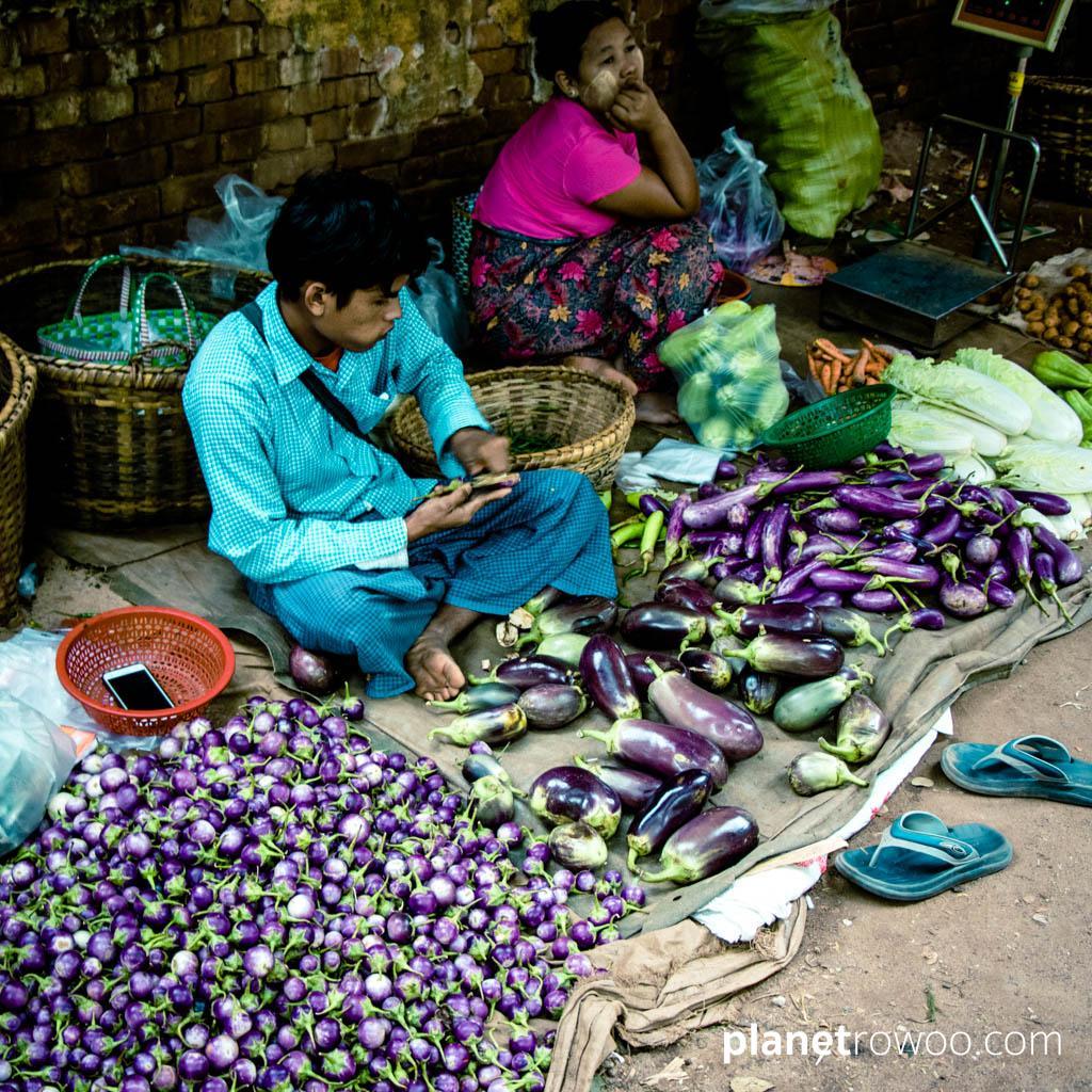 A market vendor sits amongst purple eggplants, Nyaung U market