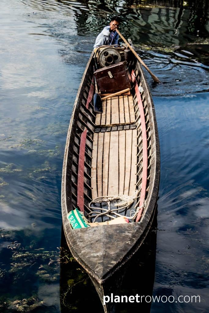 Inle Lake boatsman steers his boat through the still waters