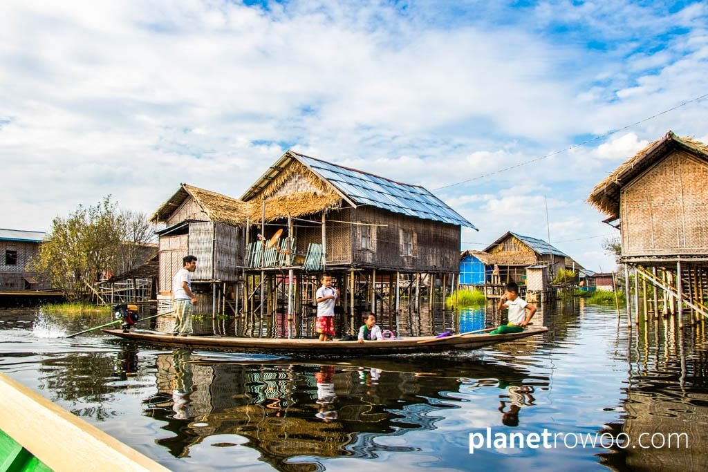 A father takes his children home after school on Inle Lake