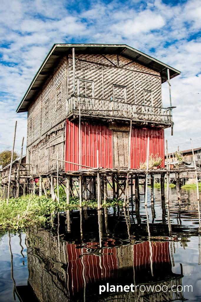 Village house reflecting in the Inle Lake waters