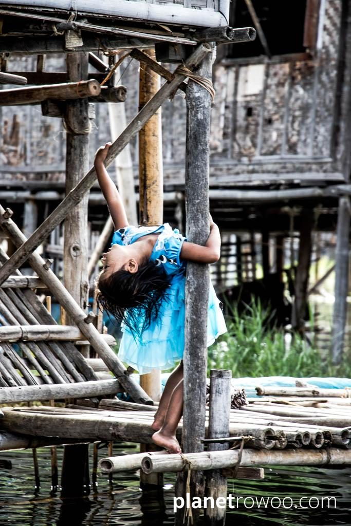 A young girl plays on her porch over the water, Inle Lake