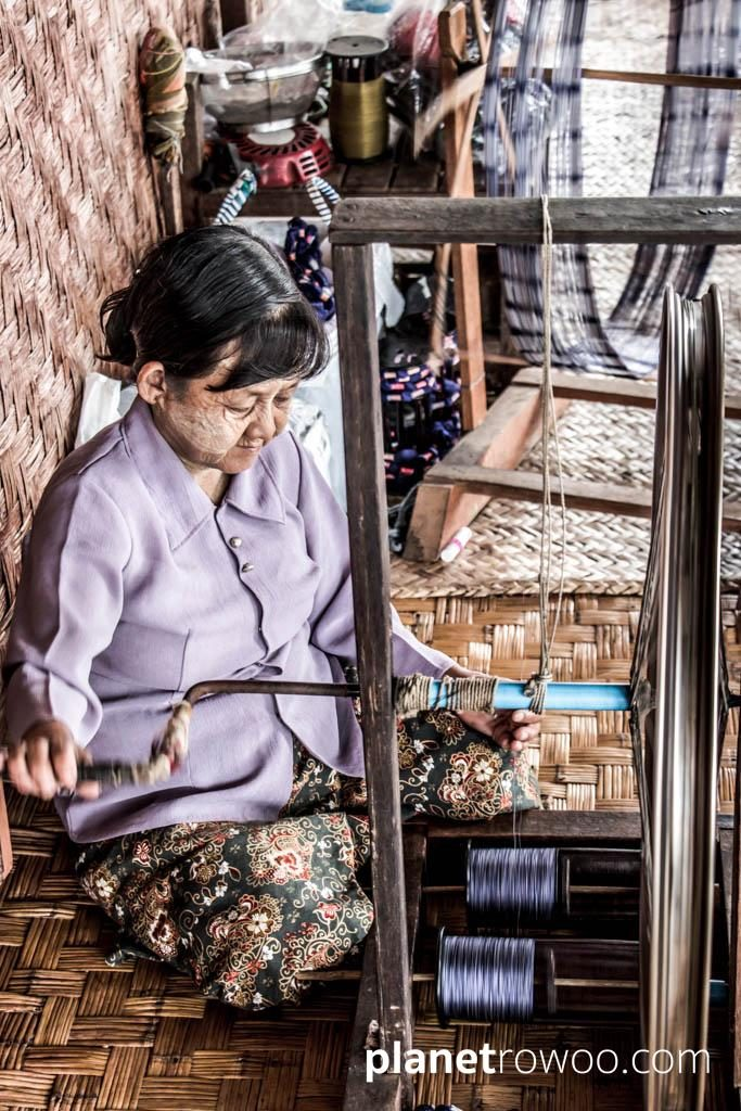Spinning the silk thread on a spinning wheel with bicycle wheel, Inpawkhone weaving village