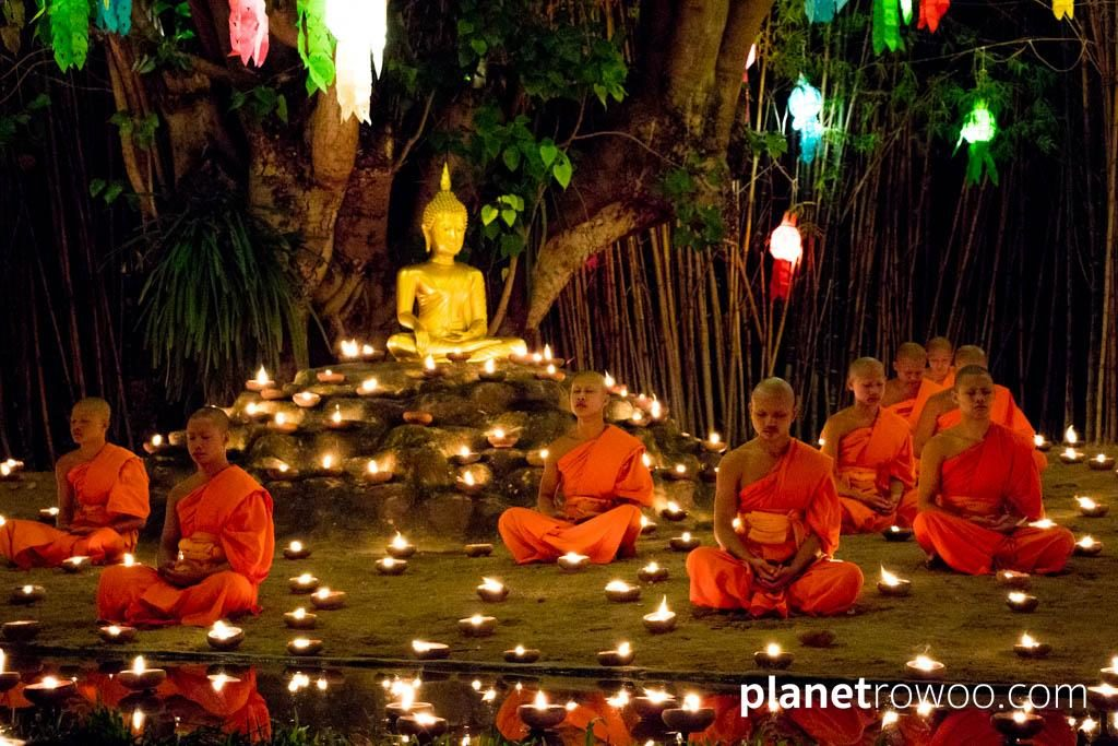 Novice monks meditate around the golden Buddha at Wat Phan Tao during the Yee Peng ceremony