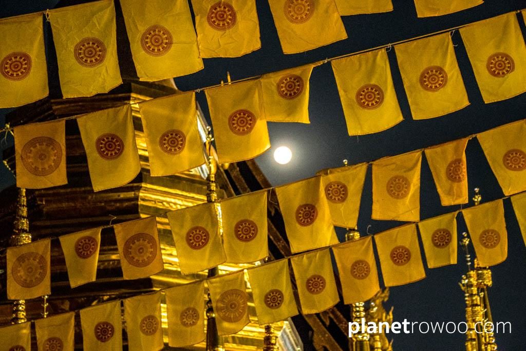The full moon shines through Buddhist dharma wheel flags on Makha Bucha Day