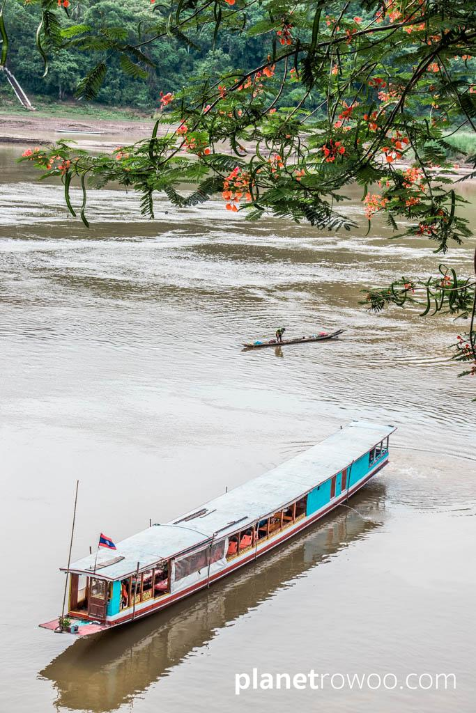 A traditional Laos long boat crosses the Mekong River at Luang Prabang