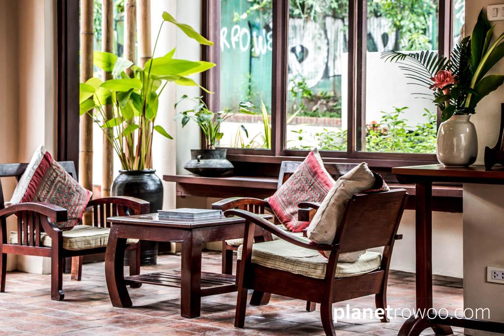 Colonial style solid wooden furniture and Laos textiles adorn the reception area at Maison Dalabua, Luang Prabang