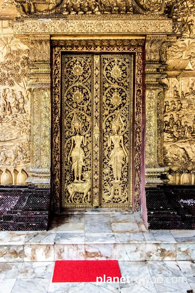 Intricate gilded reliefs adorn the exterior wall and doors of the Wat Mai sim in Luang Prabang